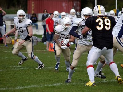 Quarterback Ben Denton hands the ball off to runningback Rob Johnson